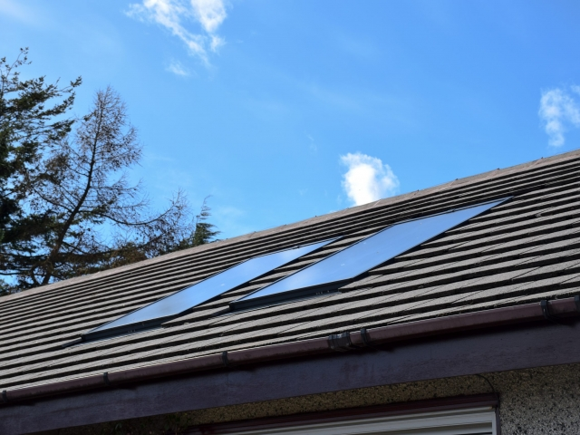 Close up of a roof with two solar panels and blue sky