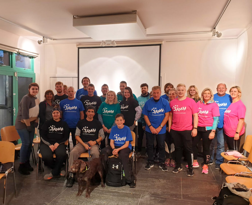 A large group pose for a photo wearing bright coloured charity t-shirts