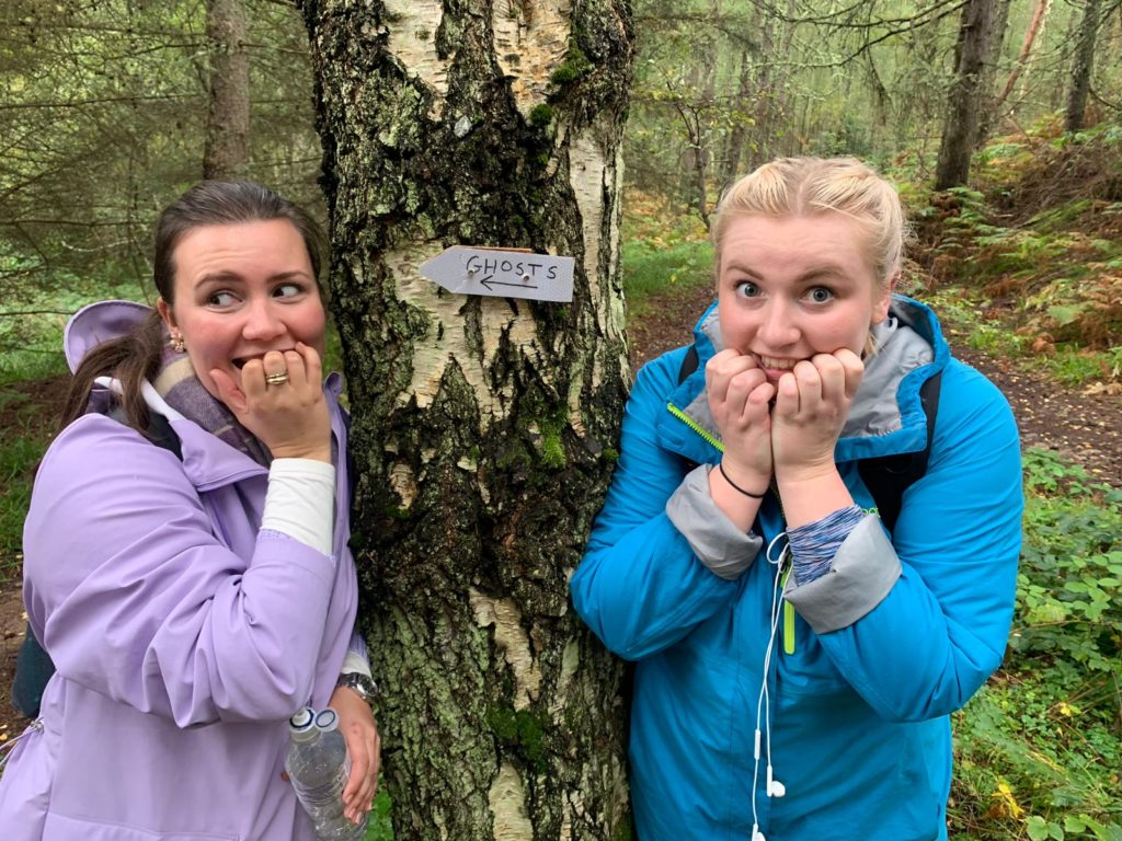 Two women stand next to a tree looking mock scared with a metal sign saying ghosts written on it