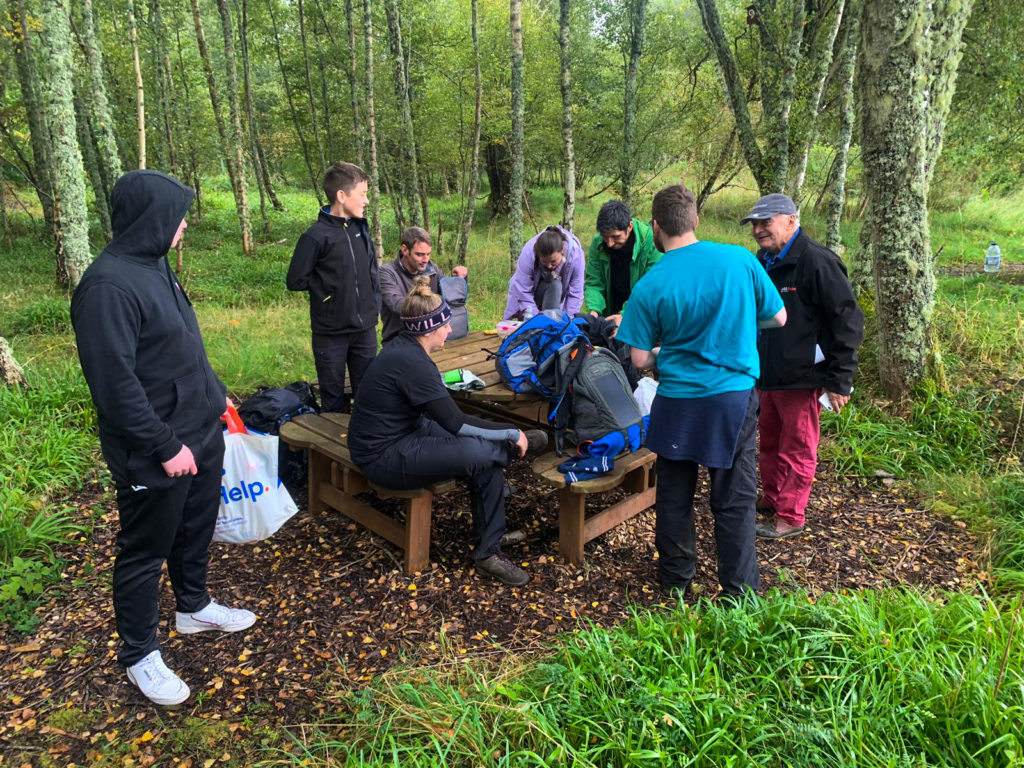 A group of people gather round a picnic table in the forest